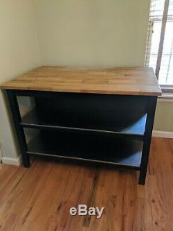 Butcher block table with stainless steel shelves and seating for 2